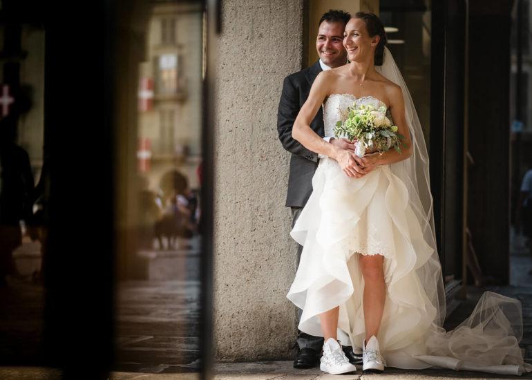 Fotografo di matrimonio Asti sposi sorridenti sotto i portici di Piazza San Secondo