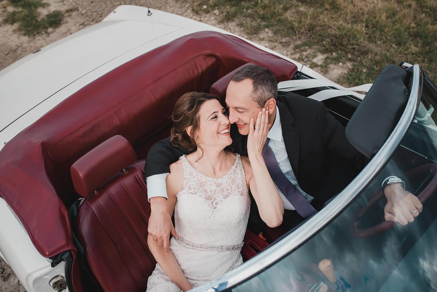 Fotografo di matrimonio Asti sposi che si abbracciano in una fiat spider cabriolet sulle colline di Zonin a Calliano