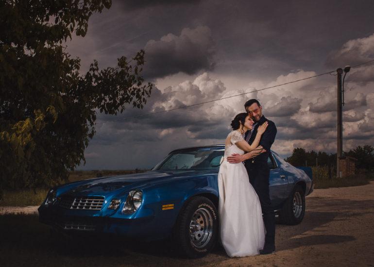 Fotografo di matrimonio Asti - sposi che si abbracciano vicino ad una Camaro blue nel giorno del loro matrimonio sotto un cielo tempestoso