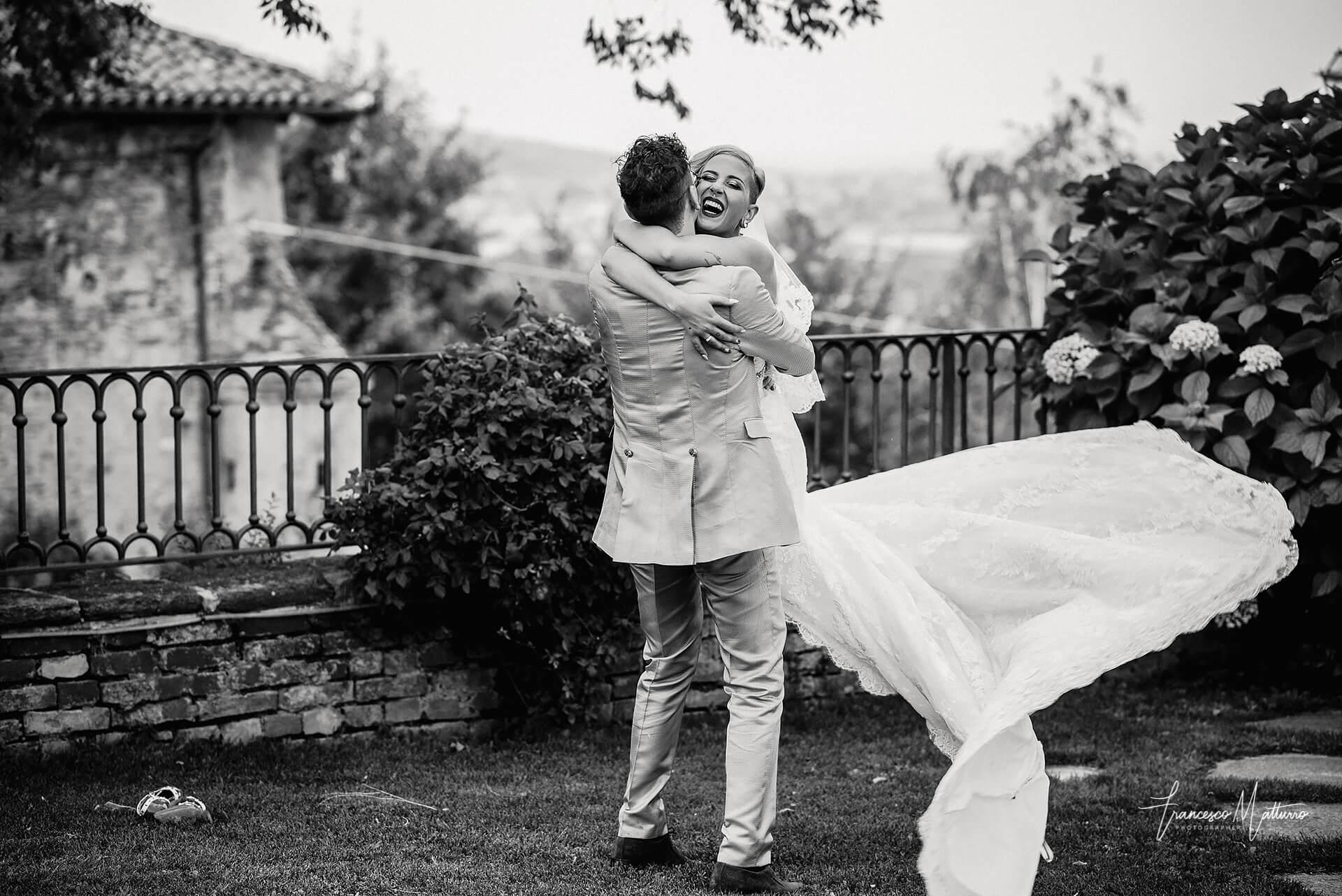 Fotografo di matrimonio Asti - foto in bianco e nero di due sposi che si stringono in un abbraccio, lui solleva lei e la fa volteggiare mentre sorride nel parco del castello rosso di costigliole saluzzo di Francesco Matturro