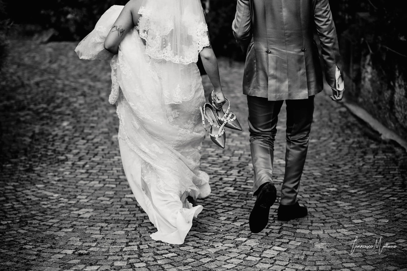 sposa che cammina con le scarpe con borchie in mano per la fatica di fianco al suo sposo si avviano al castello rosso di costigliole saluzzo di Francesco Matturro