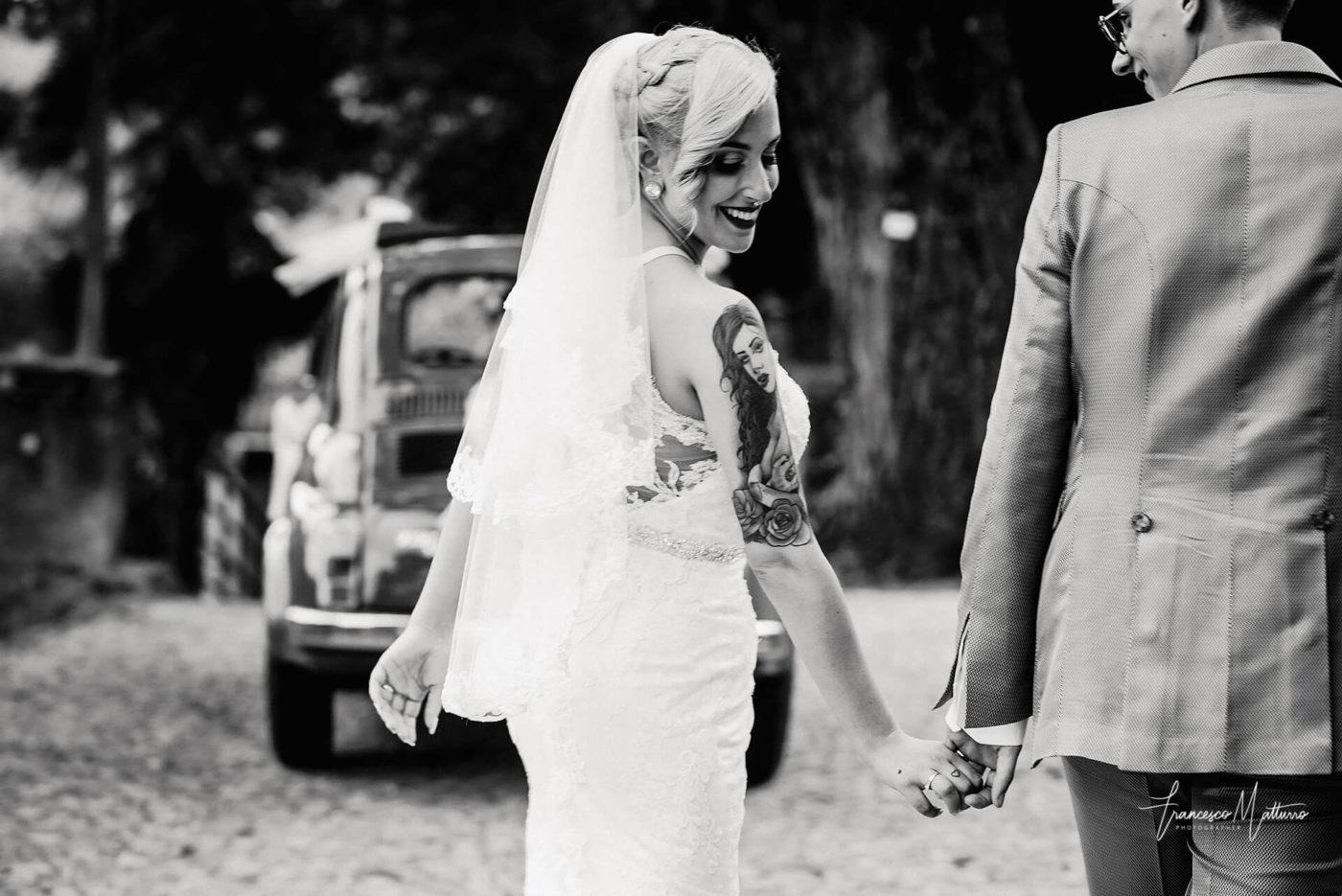 fotografia in bianco e nero di sposi che ti tengono per mano con sullo sfondo una fiat 500 d'epoca la sposa ha un tatuaggio pin up di Francesco Matturro