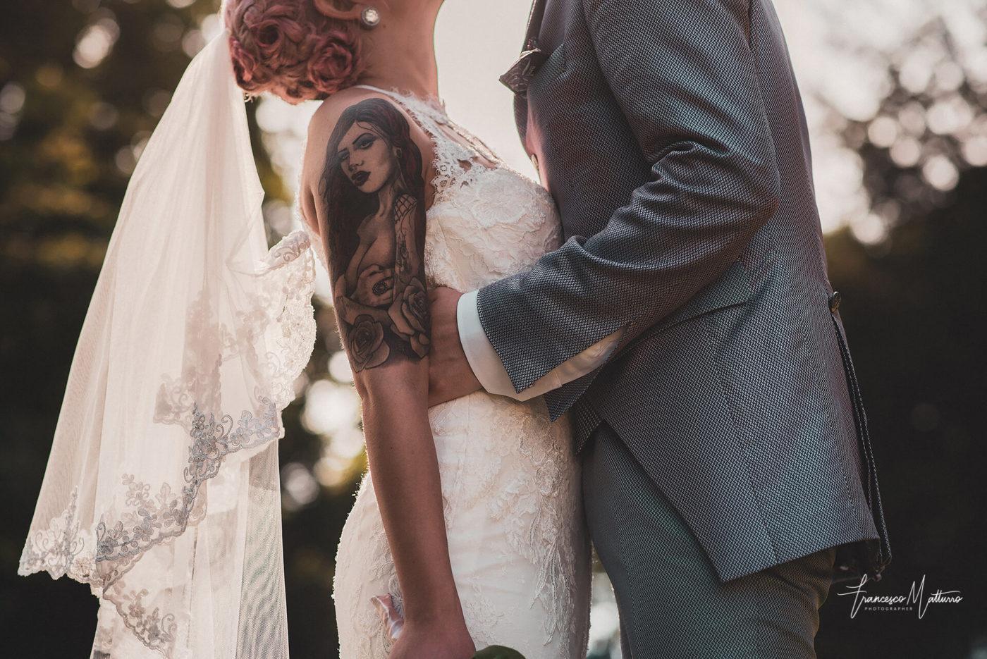 foto di coppia di sposi con tatuaggio che si baciano nel giardino del castello rosso di costigliole saluzzo di Francesco Matturro